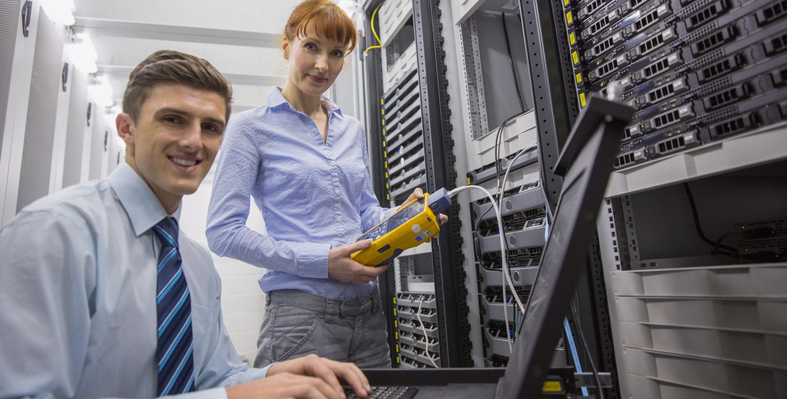 Zwei Techniker, männlich und weiblich, im Serverraum und analysieren Daten.